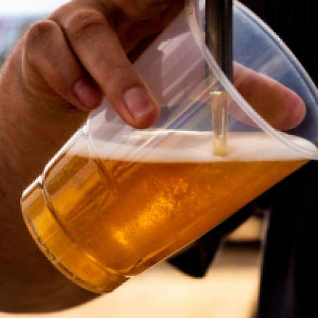 person pouring beer on clear cup